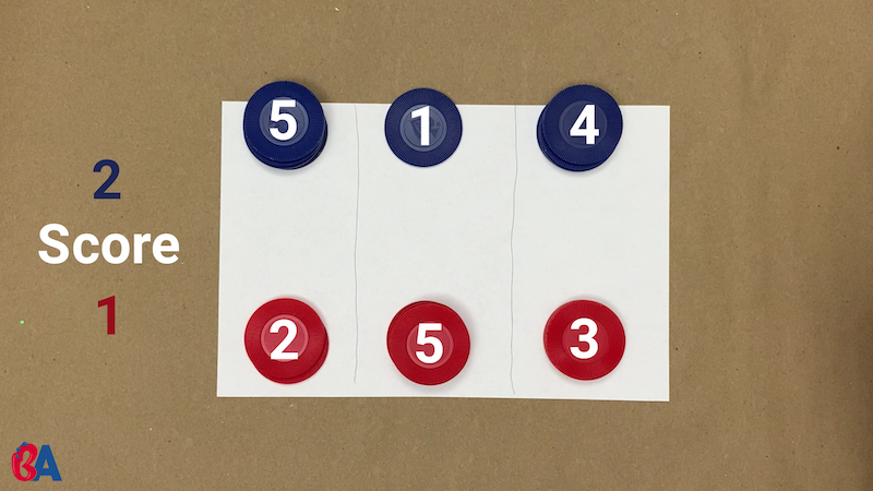 Paper divider set up between red and blue tokens