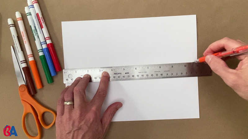 Tracing a line across the center of a paper with a ruler