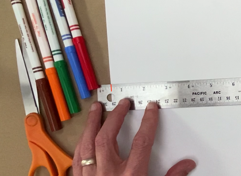 A ruler lined up with the edge of a paper at the half inch mark