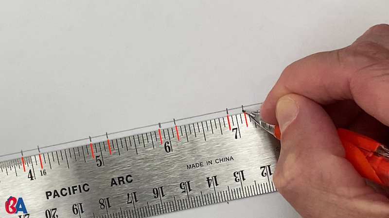 Marking along a ruler at an eighth above and below each inch mark