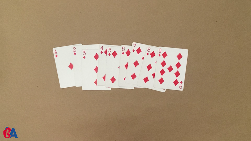 Playing cards ace through nine layed out in a row