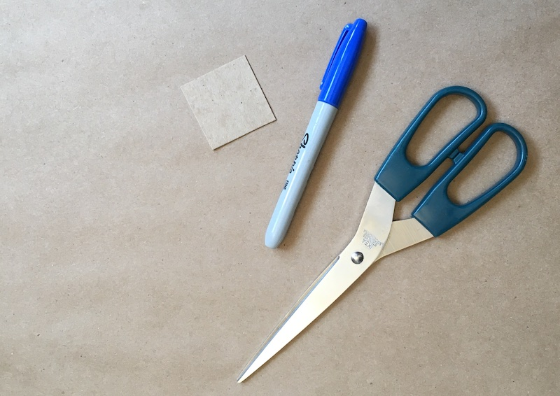 Square of cardboard, a marker, and scissors