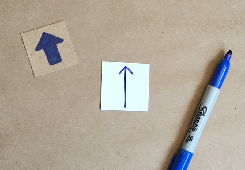 An arrow drawn on a square of paper
