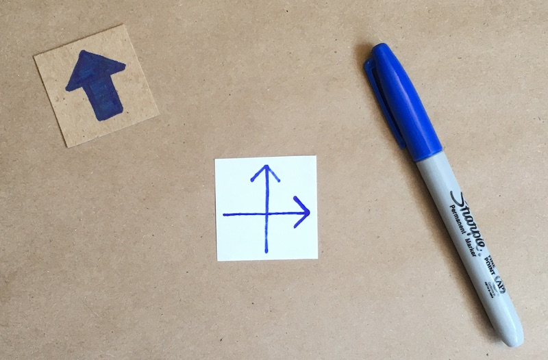 An arrow drawn on the back of the square of paper