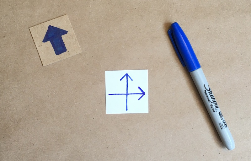 An arrow showing through a square of paper, with another arrow drawn on the front