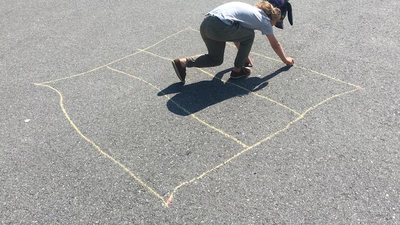 A kid drawing a grid with sidewalk chalk