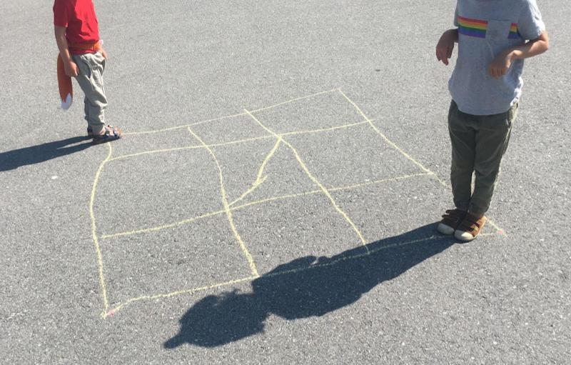 Kids standing at opposite corners of a sidewalk chalk grid
