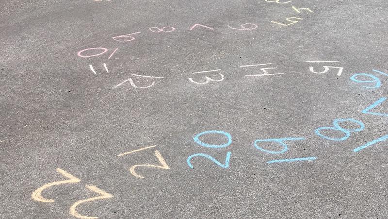 Numbers written in sidewalk chalk in a curvy path