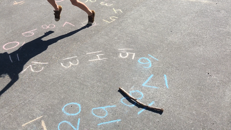 A stick set on a number while a kid jumps