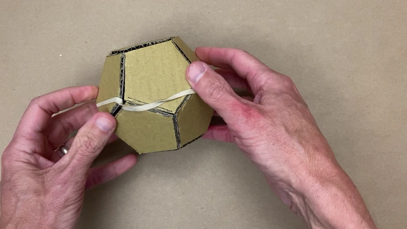 Cardboard dodecahedron with a rubber band around it