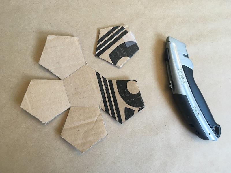 One pentagon cut from a cardboard cutout of six pentagons