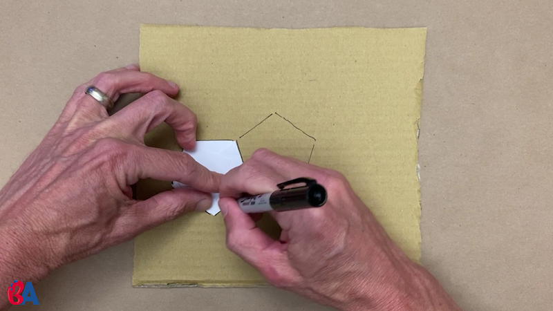 Tracing the paper pentagon onto cardboard