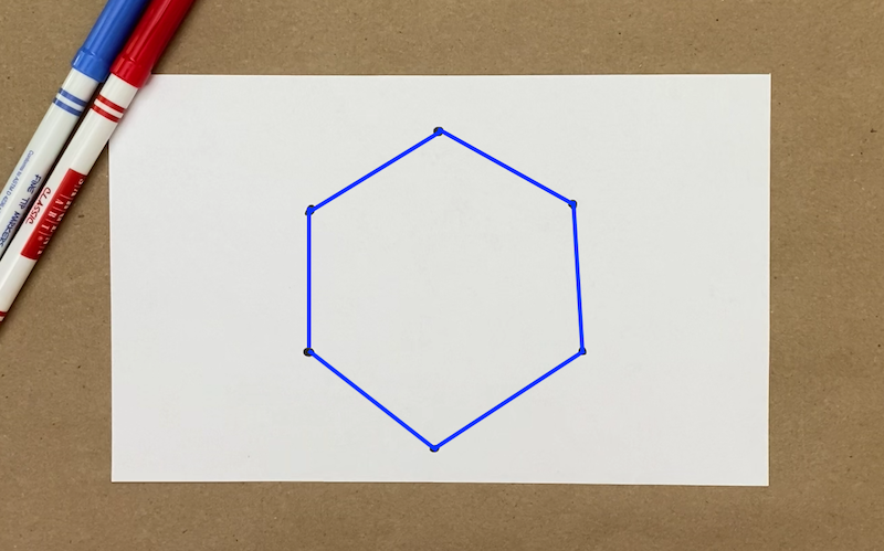 Six dots on a piece of paper with lines connecting them to make a hexagon