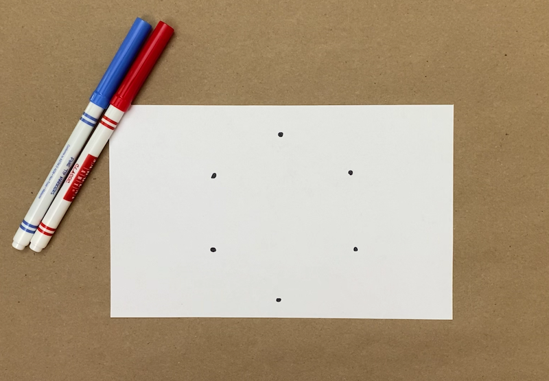 Six dots drawn on a piece of paper