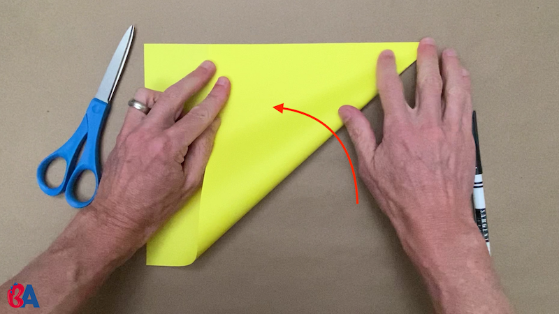 Folding the corner of a piece of paper up to make a square