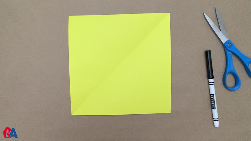 Square of yellow paper with scissors