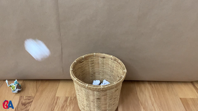 Paper ball being thrown in a waste basket